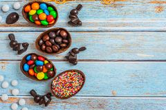 Flat lay composition with Chocolate Easter eggs, rabbit and sweets on blue wooden background. Top view. With copy space royalty free stock image