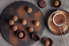 Flat lay composition with chocolate truffles and cocoa powder. On grey background royalty free stock images
