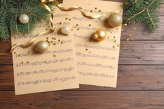 Flat lay composition with Christmas decorations and music sheets. On wooden background royalty free stock photo