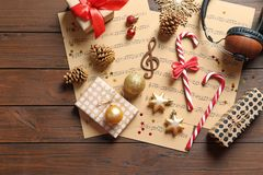 Flat lay composition with Christmas decorations, music sheets and headphones. On wooden background stock image