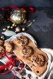 Flat lay composition with christmas toys and home made chocolate cookies on wooden board and dark background. Copy space stock image
