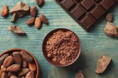 Flat lay composition with cocoa powder and chocolate bar stock image