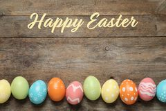 Flat lay composition of colorful painted eggs and text Happy Easter