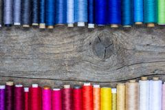 Flat lay composition with colorful sewing threads on wooden background. Copy space royalty free stock photos