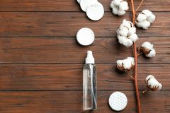 Flat lay composition with cotton pads, flowers and bottle of cosmetic product. On wooden background. Space for text stock photos