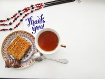 Flat lay composition with cup of black tea, peace of cake and calligraphy lettering of Thank you Royalty Free Stock Image