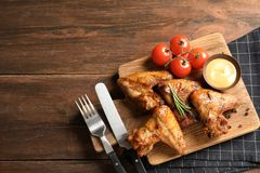 Flat lay composition with delicious barbecued chicken on wooden background. Space for text royalty free stock photos