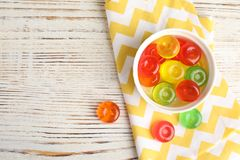 Flat lay composition with delicious colorful candies and space for text. On wooden background stock photography