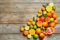 Flat lay composition with different citrus fruits on wooden background. Flat lay composition with different citrus fruits and space for text on wooden background stock image