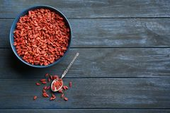 Flat lay composition with dried goji berries on blue wooden table. Healthy superfood. Flat lay composition with dried goji berries on blue wooden table, space stock photo