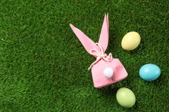Flat lay composition of Easter bunny gift bag and dyed eggs on green grass. Space for text stock photos