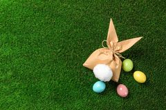 Flat lay composition of Easter bunny gift bag and dyed eggs on green grass. Space for text stock image
