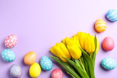 Flat lay composition with Easter eggs and flowers on color background, space for text stock images