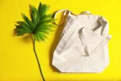 Flat lay composition with eco tote bag and leaf. On color background royalty free stock image