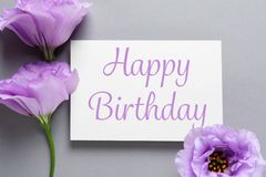 Flat lay composition of Eustoma flowers and card with greeting HAPPY BIRTHDAY. On grey background stock image
