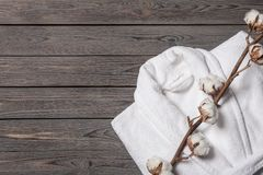 Flat lay composition with folded bathrobe and cotton flowers on wooden background. Space for text royalty free stock photo