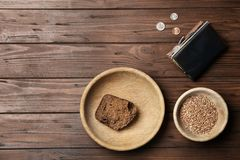 Flat lay composition with food, coins and space. For text on wooden background. Poverty concept stock images