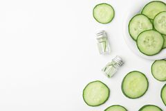Flat lay composition with fresh cucumber skin care. Tonic and bottles on white background stock photos
