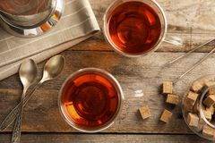 Flat lay composition with glass cups of black tea. On wooden table royalty free stock images
