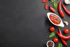 Flat lay composition with gravy boat of hot chili sauce and different spices. On dark background stock photos