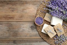 Flat lay composition of handmade soap bars with lavender flowers on brown wooden background