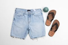 Flat lay composition with jean shorts and slippers. On white background stock photo