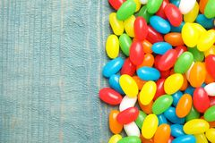 Flat lay composition with jelly beans on color background. Space for text royalty free stock photography