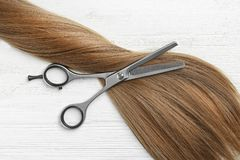 Flat lay composition with light brown hair and thinning scissors on white wooden background. Hairdresser service stock photography