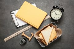 Flat lay composition with lunch box, sandwich. And stationery on grey background Stock Images