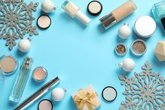 Flat lay composition with makeup products and Christmas decor on color background stock photos