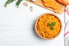 Flat lay composition with mashed sweet potatoes on wooden background. Space for text stock images