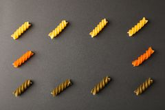 Flat lay composition with multicolored pasta on black background. Space for text stock image