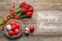 Flat lay composition of nest with painted eggs and text Happy Easter