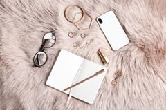 Flat lay composition with notebook, smartphone. And stylish accessories on fur. Blogger concept royalty free stock photos