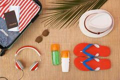 Flat lay composition with open suitcase and beach items. On bamboo mat stock image