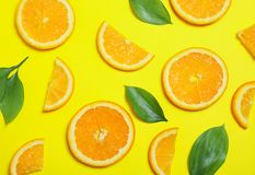 Flat lay composition with oranges and leaves on yellow background royalty free stock photography