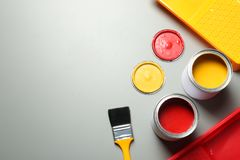 Flat lay composition with paint cans and brush on grey background. Space for text stock photography