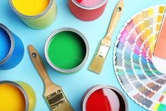 Flat lay composition with paint cans, brushes. And color palette on blue background royalty free stock photos