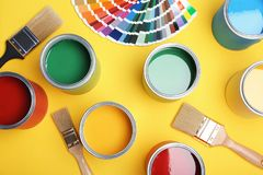 Flat lay composition with paint cans, brushes and color palette. On yellow background stock image