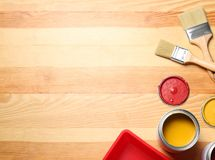 Flat lay composition with paint cans and brushes on wooden background. Space for text royalty free stock image