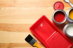 Flat lay composition with paint cans and brushes on wooden background. stock image