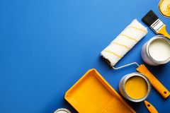Flat lay composition with paint cans, decorator tools and space for text. On color background royalty free stock images