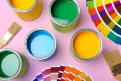 Flat lay composition with paint cans. Brushes and color palettes on pink background stock photos