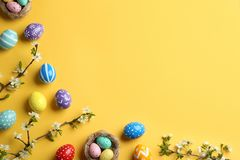 Flat lay composition with painted Easter eggs and blossoming branches on color background. Space for text royalty free stock image