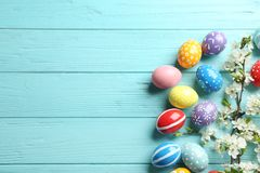 Flat lay composition with painted Easter eggs and blossoming branches on wooden background. Space for text stock photo