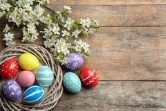 Flat lay composition with painted Easter eggs and blossoming branches on wooden background. Space for text stock images
