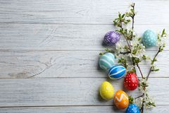 Flat lay composition with painted Easter eggs and blossoming branches on wooden background. Space for text royalty free stock photos