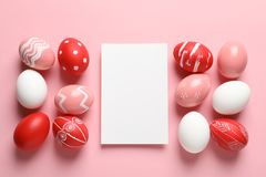 Flat lay composition of painted Easter eggs and card on color background. Space for text royalty free stock photography