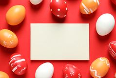 Flat lay composition of painted Easter eggs and card on color background. Space for text royalty free stock images