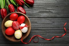 Flat lay composition of painted Easter eggs and flowers on wooden table, space for text. Flat lay composition of painted Easter eggs and spring flowers on wooden royalty free stock image